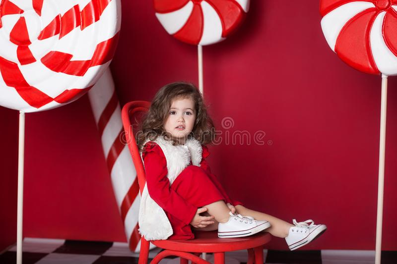 New Year 2020! Christmas, holidays and childhood concept. Merry Christmas, happy holidays! Little curly girl is sitting on chair w royalty free stock images