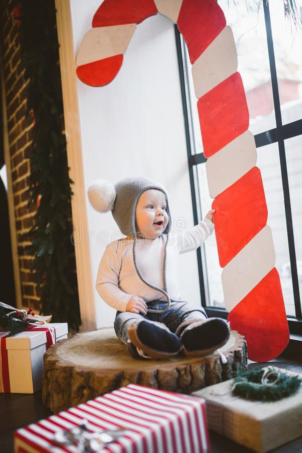 New year and Christmas holidays theme Caucasian child boy 1 year old sitting on a stump felled tree near the window in a funny hat royalty free stock photo