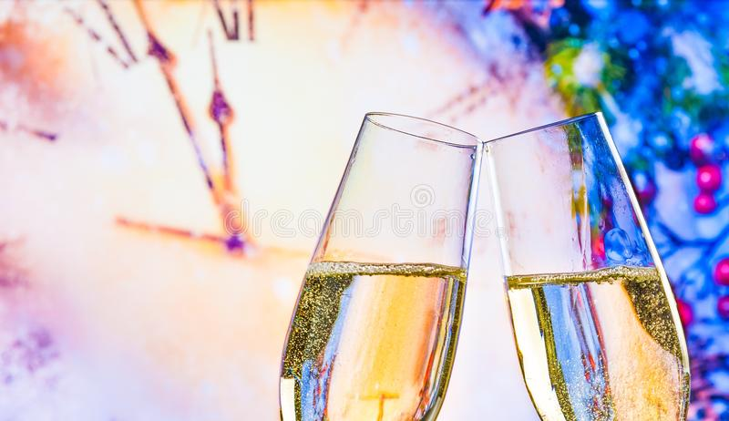 New Year or Christmas at midnight with champagne flutes make cheers on clock background. New Year or Christmas at midnight with champagne flutes make cheers on stock photography