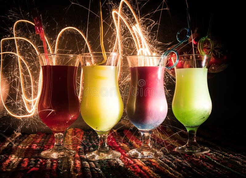 Different tasty cocktails with creative New Year holiday artwork decoration on background. Colorful cocktail in glass. Party club. New Year and Christmas party royalty free stock image