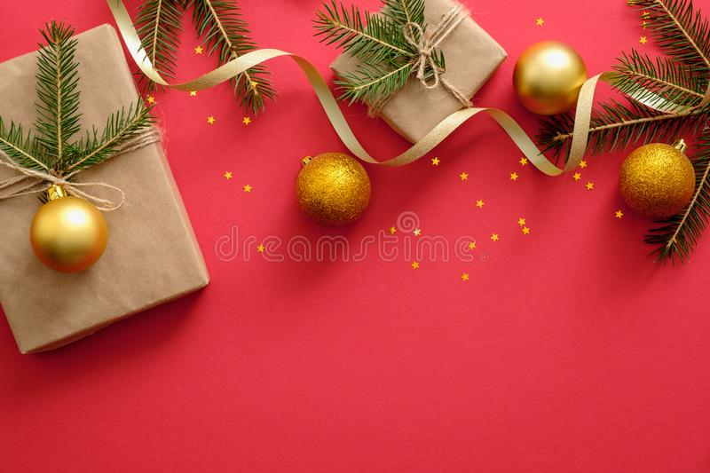 New Year or Christmas presents wrapped ribbon and fir tree branches, golden Christmas ball on red background. Template mockup stock images