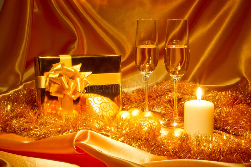 New Year Christmas still life in golden tones. New Year (Christmas) still life in golden tones with gift box, candle, satin, Christmas-tree decorations and two stock photo