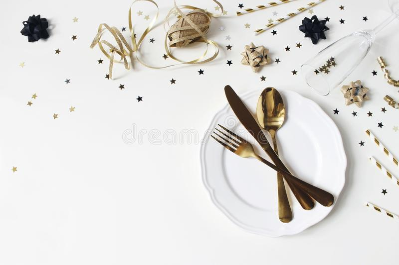 New Year, Christmas styled glamorous black and gold table setting with plate, goldenware, confetti stars and champagne royalty free stock photo