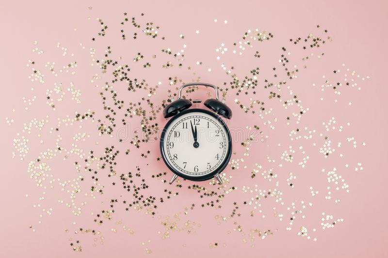 New Year Christmas Top view flat lay black alarm clock twelve covered golden stars confetti copy space millennial pink color paper. Background minimal style stock photography