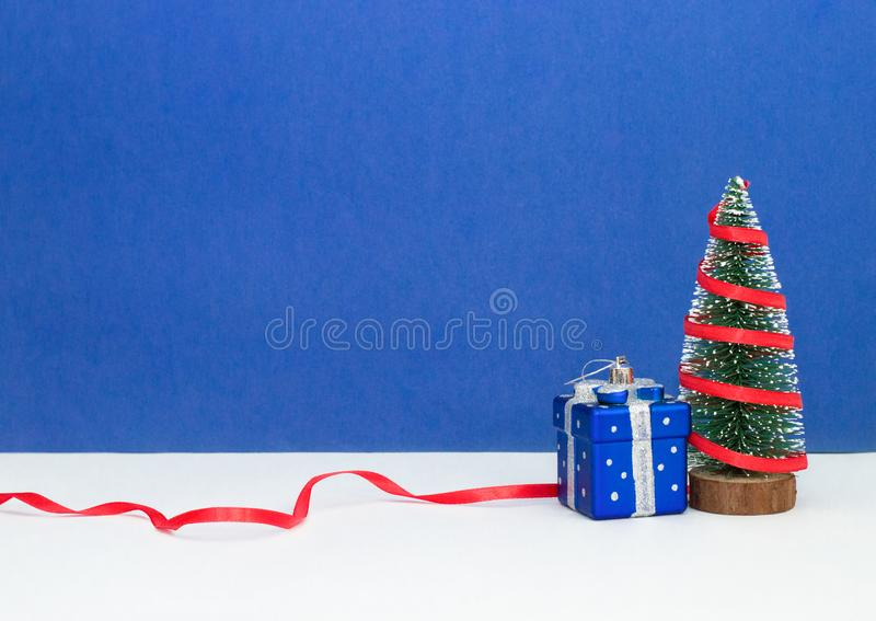 New Year Christmas tree with red atlas ribbon and big blue present box on blue background stock photos