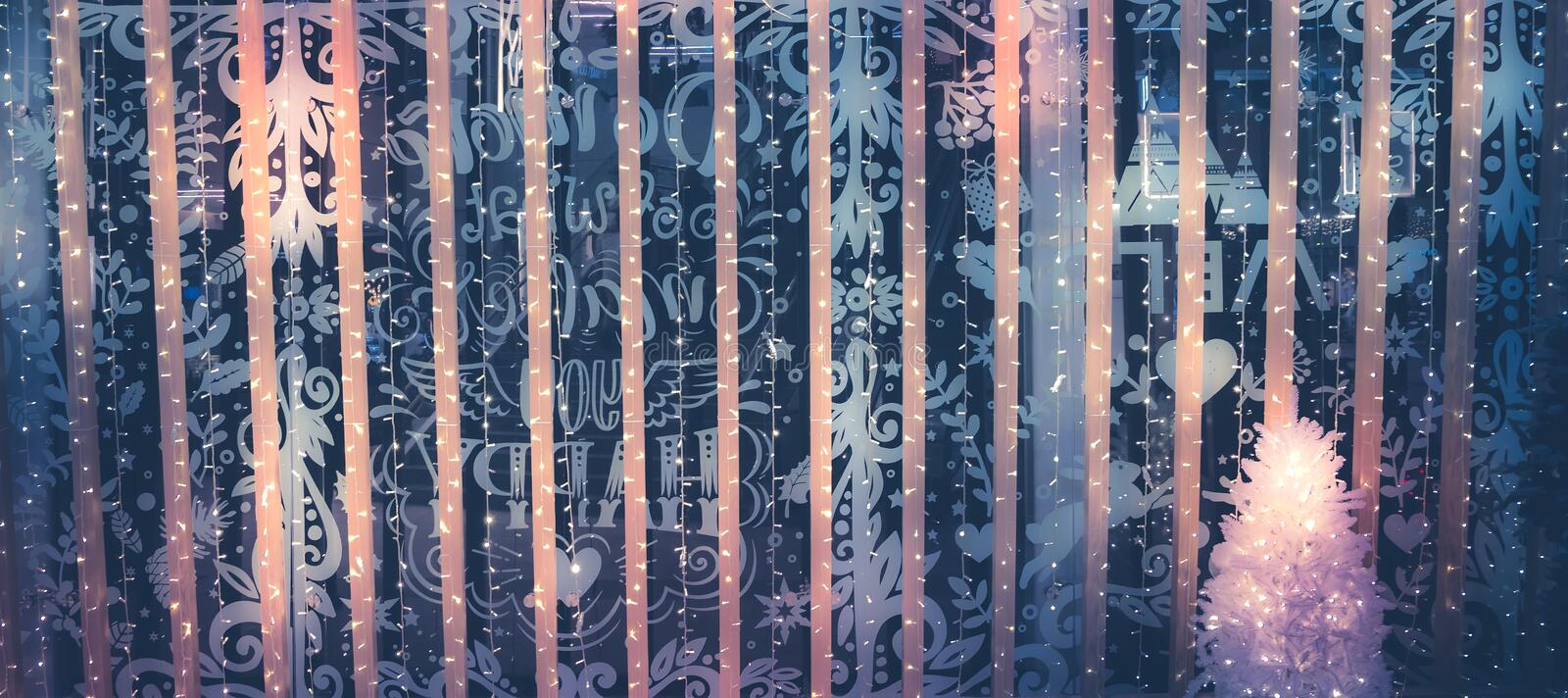 Christmas Winter night vintage background with Christmas lights and Christmas tree in gradient dark blue pink lilac colors royalty free stock image