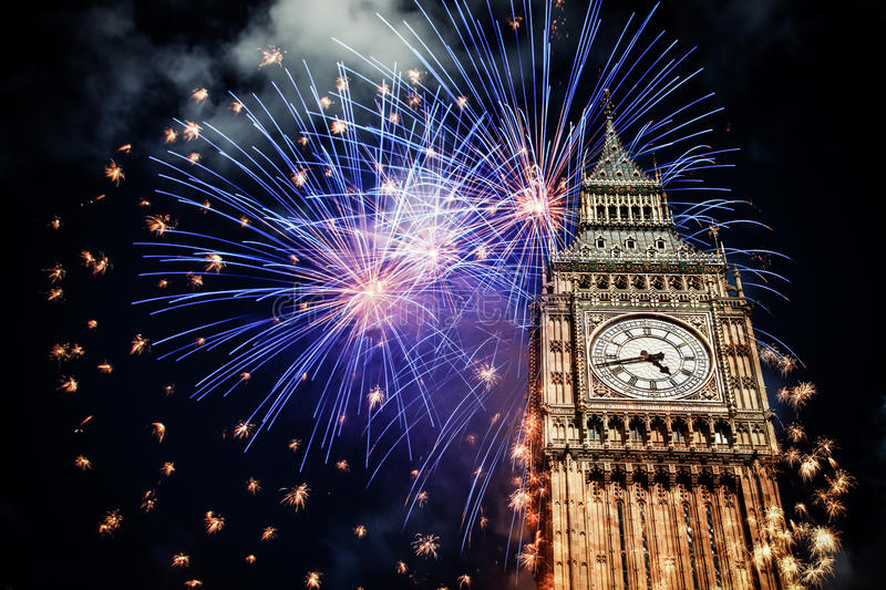 New Year in the city - Big Ben with fireworks. Explosive fireworks display fills the sky around Big Ben. New Year's Eve celebration background royalty free stock photo