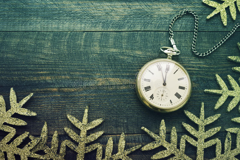 New year clock. Old pocket watch on a wooden background. New Year`s background with hours over time 23:55 stock photography