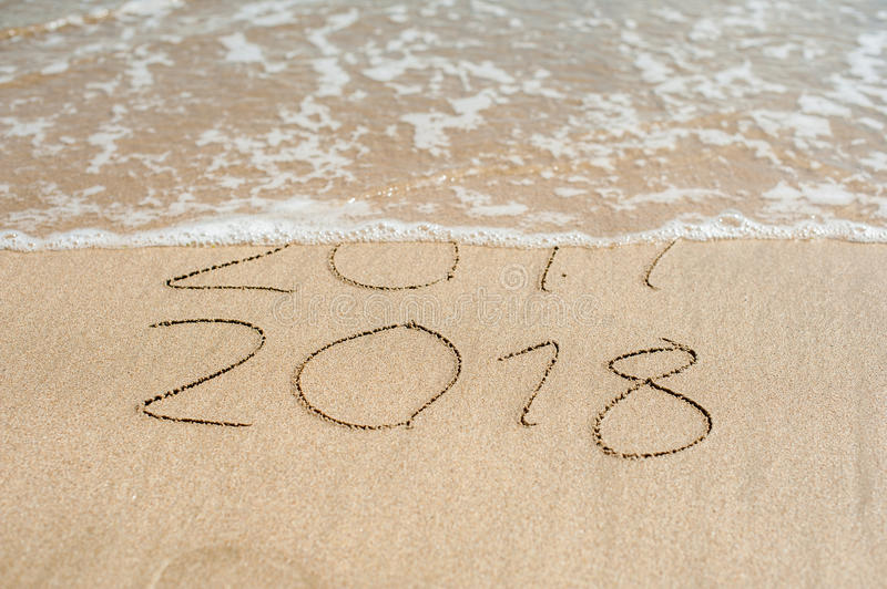 New Year 2018 is coming concept - inscription 2017 and 2018 on a beach sand, the wave is almost covering the digits 2017.  royalty free stock images