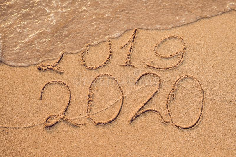 New Year 2020 is coming concept - inscription 2019 and 2020 a beach sand, the wave is almost covering the digits 2019.  stock photography