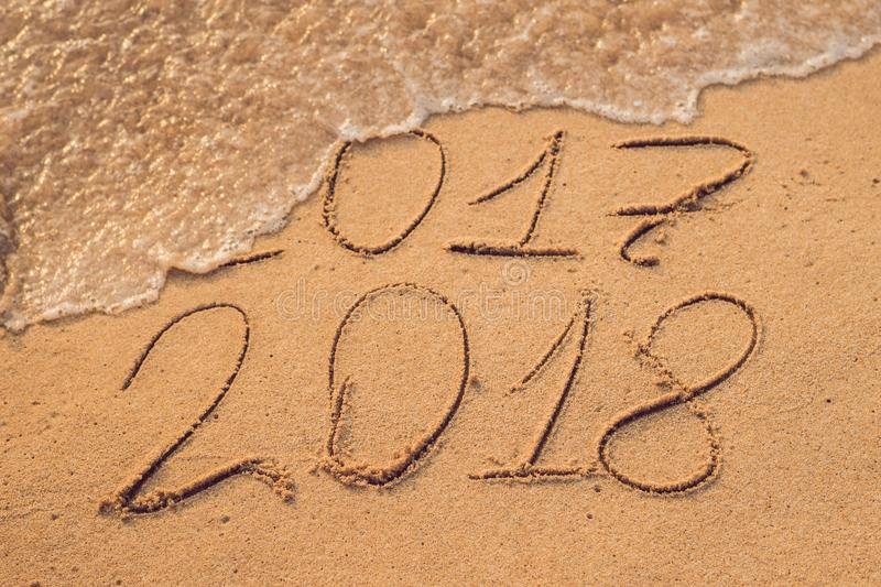 New Year 2018 is coming concept - inscription 2017 and 2018 on a beach sand, the wave is almost covering the digits 2017.  stock photo