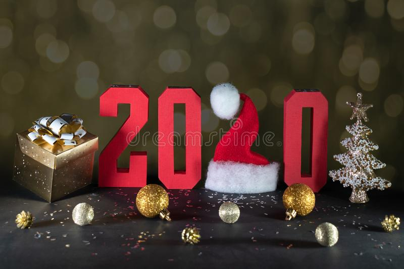 New year 2020 composition with red geometric numbers and Christmas decorations against bokeh dark background. Santa Claus hat in stock photography