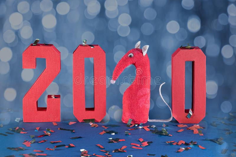 New year 2020 composition with red geometric numbers and confetti against bokeh blue background. Toy rat in the form of figure 2 stock photos