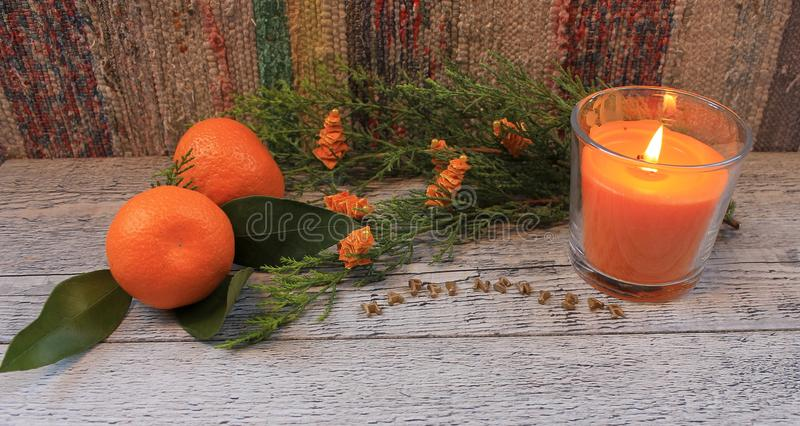 New Year composition with tangerines, arborvitae branch, candles and Christmas trees royalty free stock photo