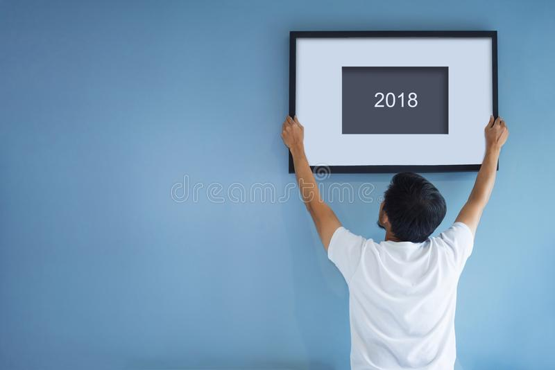 New year concept. Asian man holding a picture frame of 2018 on b royalty free stock photography