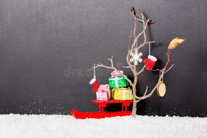 New Year concept of bare tree with mittens, boot, snowflake, Christmas ball and red festive sled, gift boxes in snow on stock images