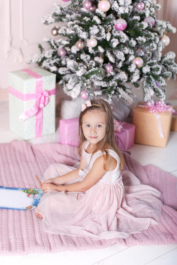 New Year 2020! The concept of Christmas, holidays and childhood. Cute little child girl writes the letter to Santa Claus near Chri stock photography
