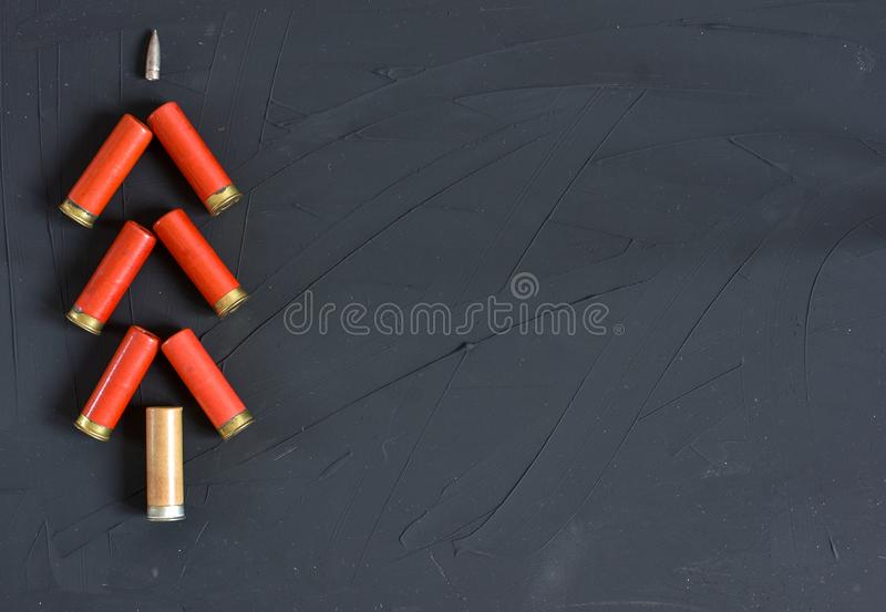 New Year concept. Congratulations for the hunter with hunting cartridges on the colored background lies as Christmas tree. Copy pa royalty free stock image