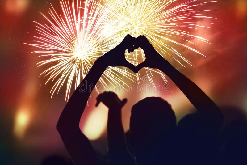 New Year concept of crowd and fireworks. Silhouette of heart shaped hands stock photo