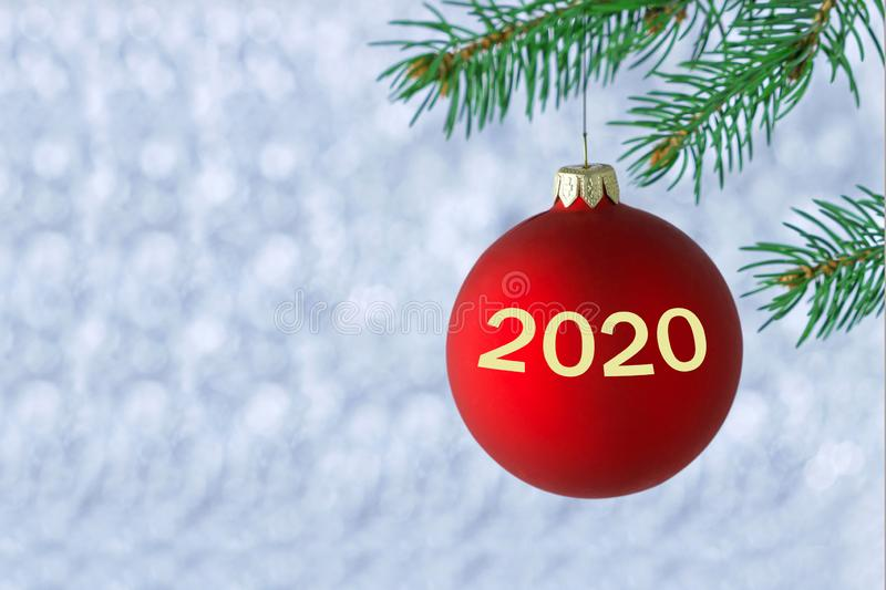 New Year 2020 concept. Magical atmosphere. Christmas ball with numbers 2020, symbol of coming new year hanged on a christmas tree stock photography