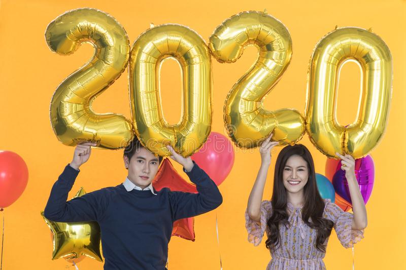 2020 New Year Concept. Portrait of smiling beautiful young asian woman and smart man holding golden number balloon and colorfull royalty free stock images