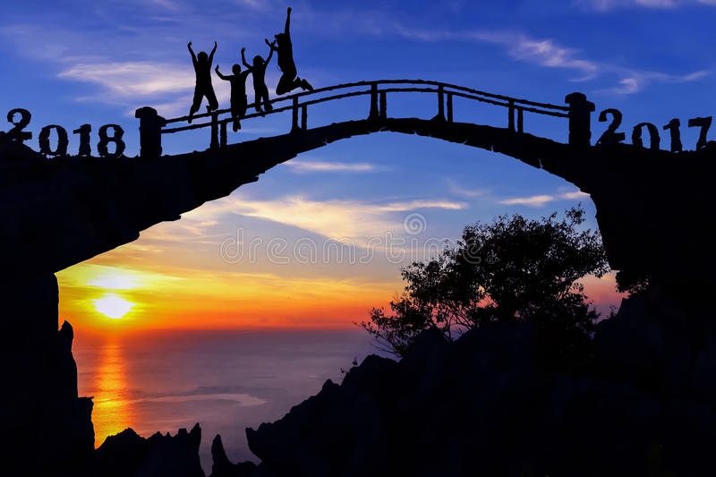 New year 2018 concept. Silhouette family jumping on the bridge. New year 2018 concept. Silhouette family jumping on stone bridge background stock photos
