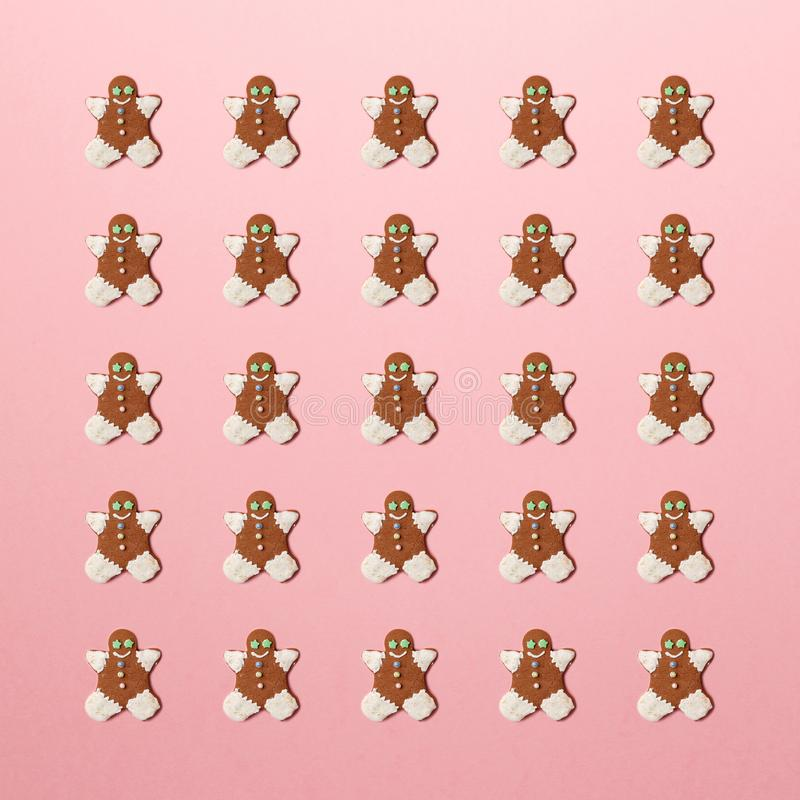 New Year concept. Trendy pattern made with Christmas gingerbread man on bright light pink background. Minimal creative concept. Creative Christmas decoration royalty free stock photography