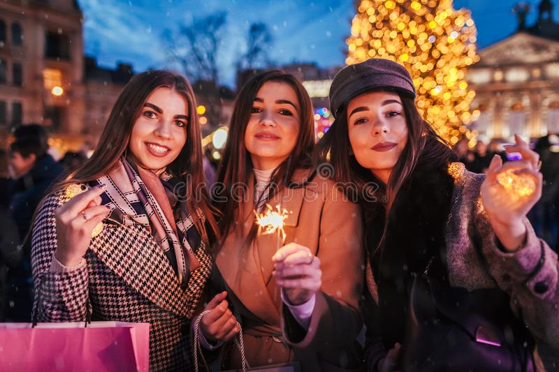 New Year concept. Women friends burning sparklers in Lviv by Christmas tree on street fair. Girls holding shopping bags stock image