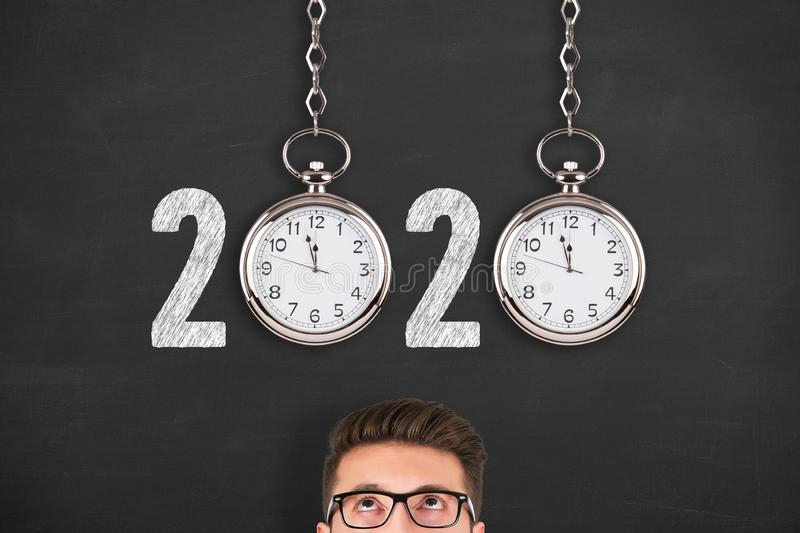 New year concepts 2020 countdown clock over human head on blackboard background. New year concepts stock photography