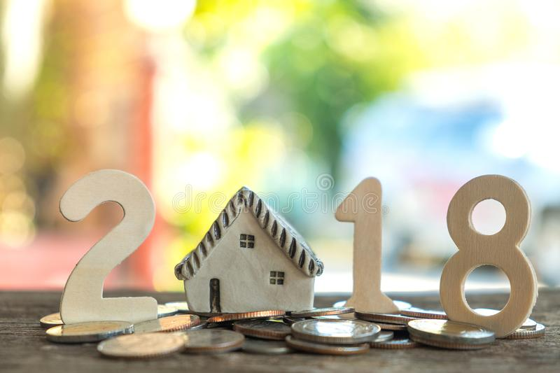 2018 New year concepts,Number two, one, eight, put on coins,Model house replaced by zero.All laid on wooden floor,Light from. The back royalty free stock photography