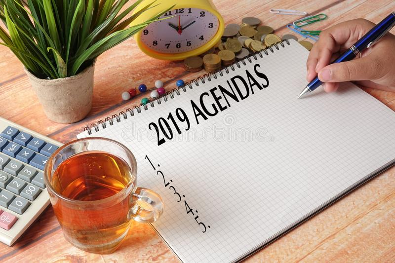 NEW YEAR CONCEPTUAL TEXT. Hand writing on notepad on a wooden ta stock photography