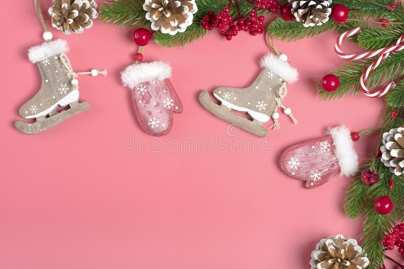 New year decor-cones, red wooden mittens, skates, green tree, snowflakes on pink background royalty free stock images