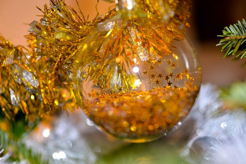 New year decor, tinsel. Glass ball toy with golden stars, orange garland royalty free stock image
