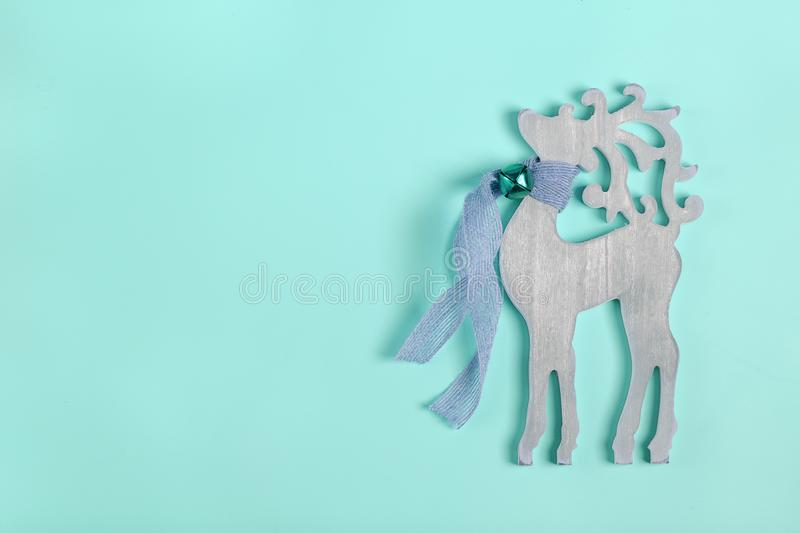 New year decor- wooden deer with a scarf and a bell around the neck on blue background royalty free stock images
