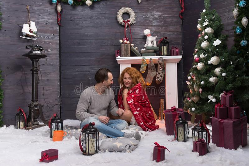 New Year decoration and romantic couple sitting near the fire place. Relaxed long haired lady covered in warm blanket sitting on the soft carpet near the royalty free stock photos