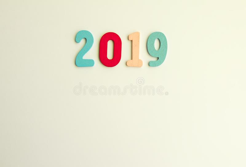 New Year decorative composition with 2019 colorful wooden small numbers. Festive card with empty space for message.  royalty free stock images
