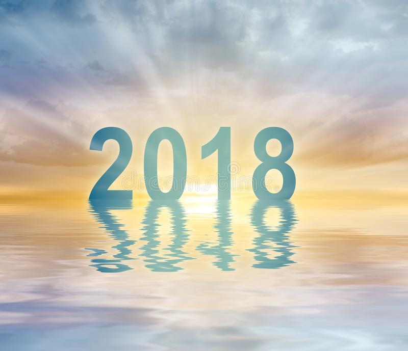 New year 2018 digits text sunset blur background. Happy new year 2018 digits text on sunset blur background reflecting in water royalty free stock photo