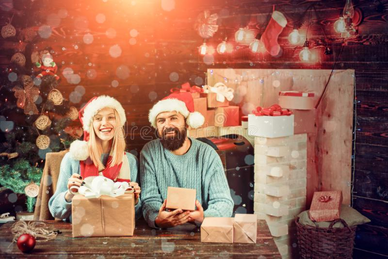 New year family with christmas present boxes in front of christmas tree. Happy couple over christmas tree lights royalty free stock image