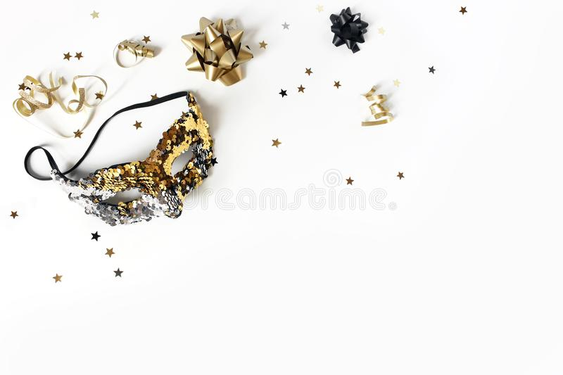 New Year festive composition with carnival mask, black and gold confetti stars and ribbons. Party decoration stock photography