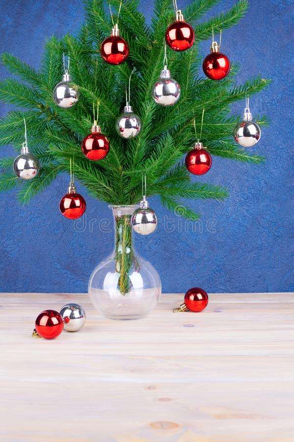 New Year festive greeting card, Christmas decorations silver and red balls on green pine branches in glass vase on wooden table stock photo