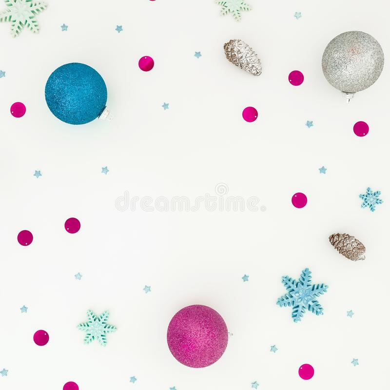 New Year frame with Christmas balls and pink confetti on white background. Flat lay, top view stock photo