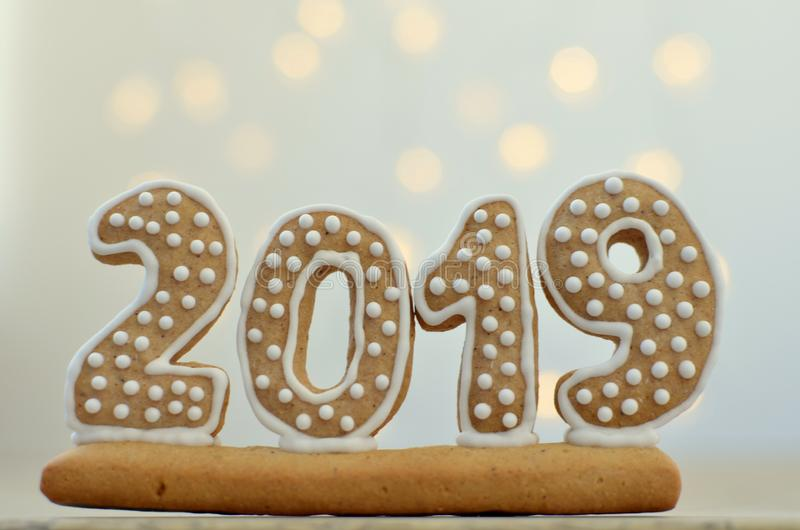 New Year 2019. Gingerbread figures on a wooden board. Christmas lights on the background. New Year greetings. Suitable as a backg stock images
