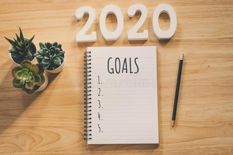 New year 2020 goals list. Office desk table with notebooks and pancil with pot plant stock photos