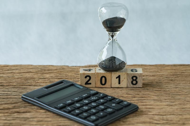 new year 2018 goals, target minimal concept as number 2018 wooden cube block with sandglass and calculator on wooden table royalty free stock image