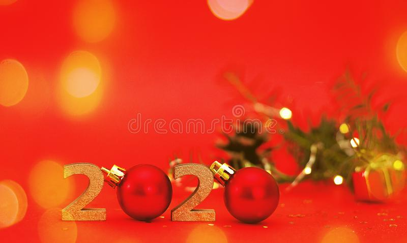 2020 New year golden number with sparkling festive christmas lights bokeh and tree branch, red background stock photo