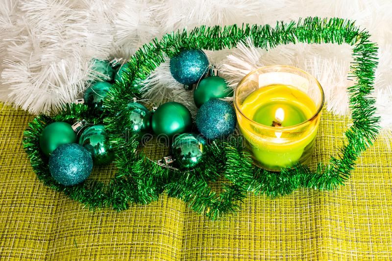 New year, green balls and decorations for the Christmas tree. Bright and beautiful scenery on a lemon background with white tinsel royalty free stock photography