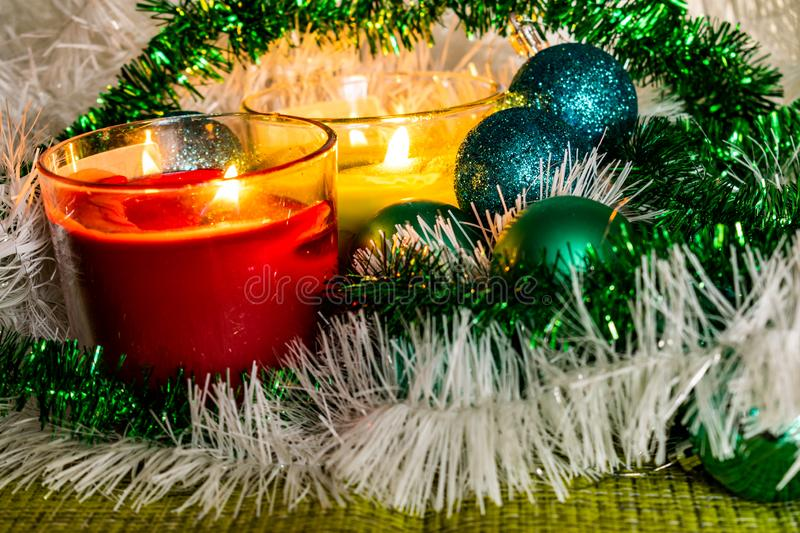 New year, green balls and decorations for the Christmas tree. Bright and beautiful scenery on a lemon background with white tinsel stock images