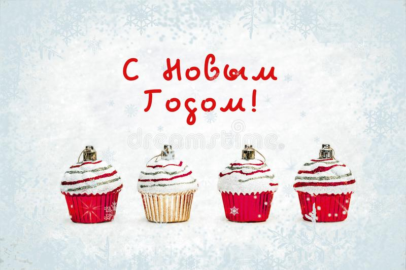 New Year greeting card - Christmas bauble cupcakes on white snow with snowflakes background. Russian translation: Happy New Year stock images