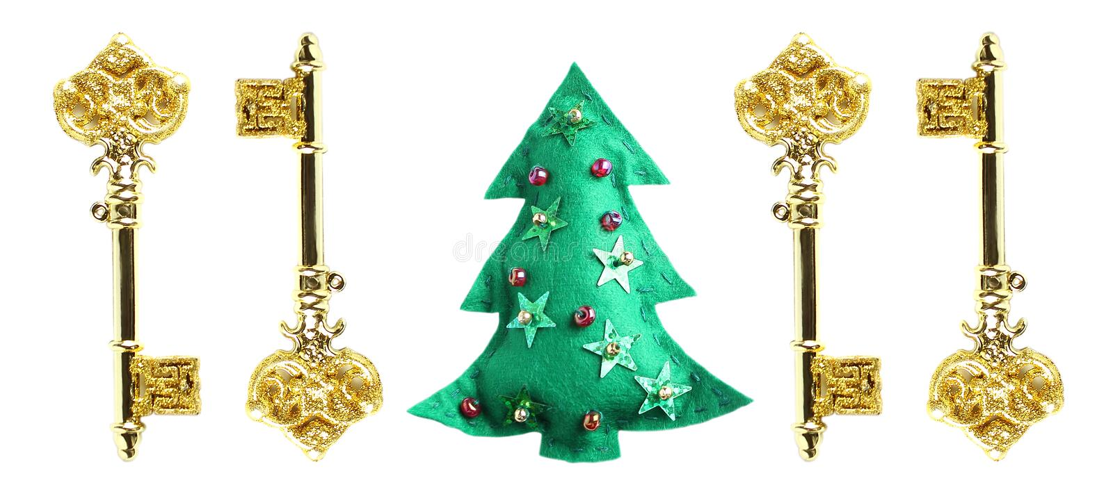New Year greeting card concept. toys made of green felt embroidered with shiny beads and gold keys. White background, flat lay, royalty free stock images