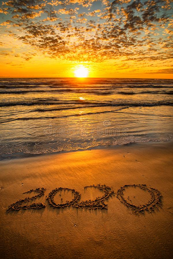 New Year 2020. Happy New Year 2020 concept, on the sea beach at sunset royalty free stock photos